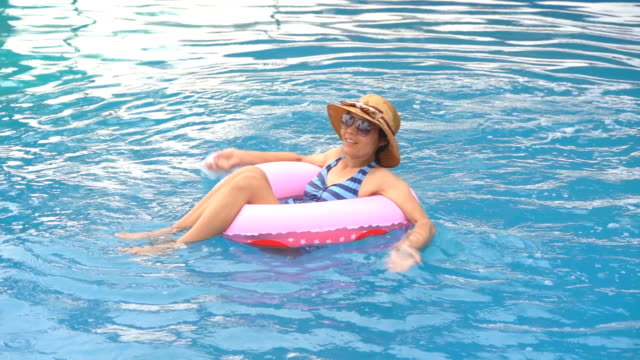 Girl-slow-motion-playing-and-swimming-on-ring-rubber-floating-on-swimming-pool