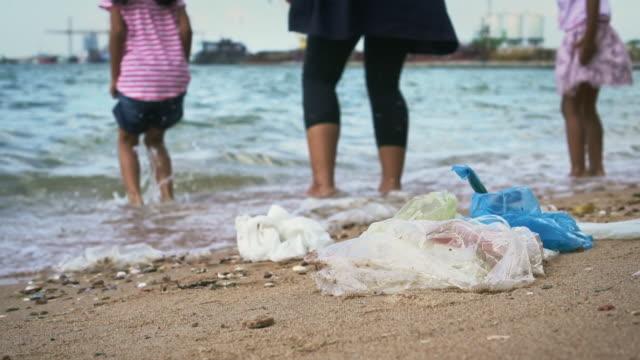 Residuos-plásticos-y-basura-con-mamá-e-hija-jugando-en-la-playa