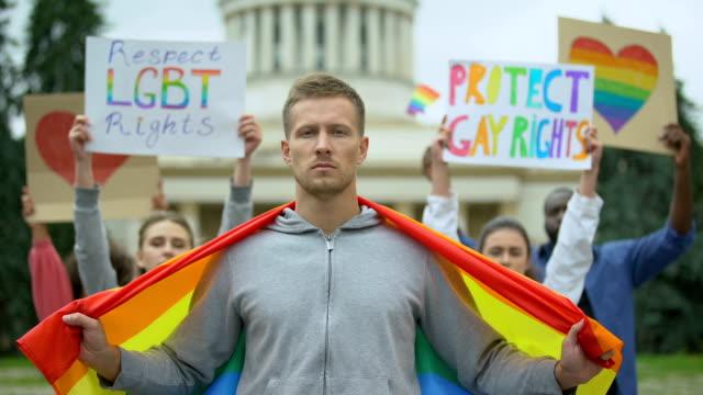 Hübscher-Mann-mit-Regenbogenflagge-inmitten-von-Demonstranten-für-Homosexuellenrechte-LGBT-Pride-Event