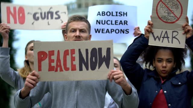Activists-waving-banners-protesting-against-mass-shootings-nuclear-weapon-war