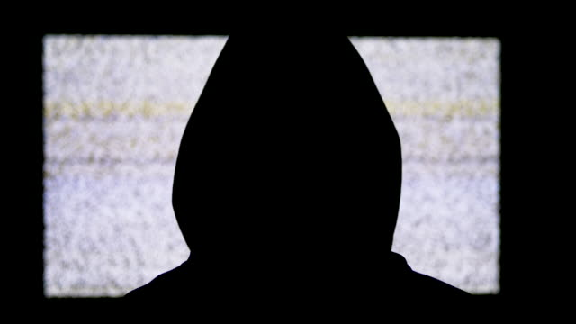 Silueta-de-la-cabeza-del-hombre-en-la-capucha-está-viendo-el-ruido-estático-blanco-y-la-interferencia-de-la-televisión