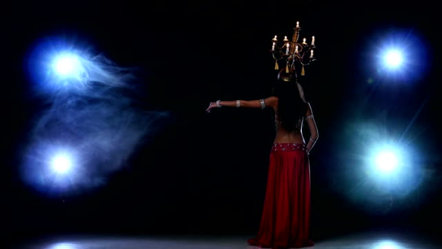 Attractive-belly-dancer-girl-go-on-dancing-with-candles-her-head-black-smoke
