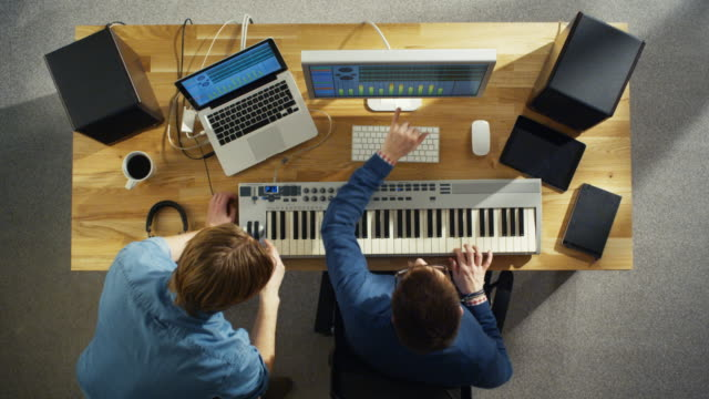 Top-View-of-Two-Audio-Engineers-Working-in-Their-Sunny-Studio-They-Play-on-a-Musical-Keyboard-and-Experiment-with-Sound-