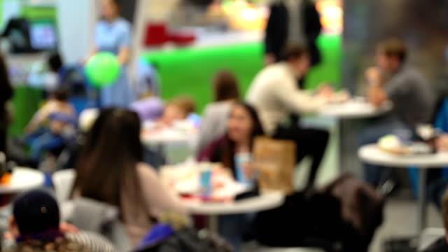Alimento-de-la-chatarra-del-concepto-Irreconocible-gente-comiendo-comida-rápida-en-patio-de-comidas-del-centro-comercial