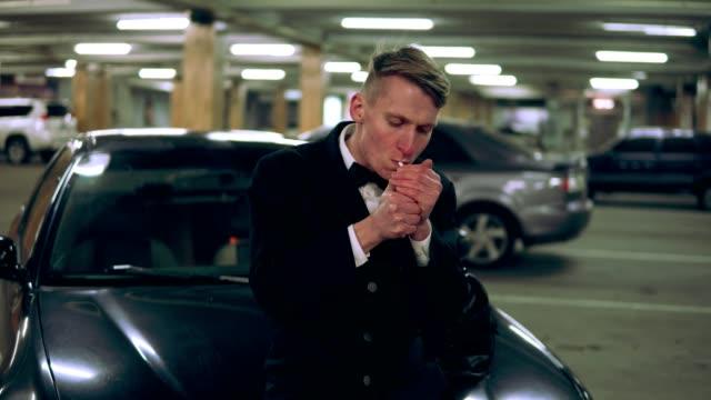Hombre-joven-en-un-traje-negro-con-pajarita-fumar-un-cigarrillo-sentado-en-el-capó-del-coche-negro-en-el-estacionamiento-Esperando-a-alguien-y-sosteniendo-un-bolso-grande-Levantarse-y-salir-Vista-frontal
