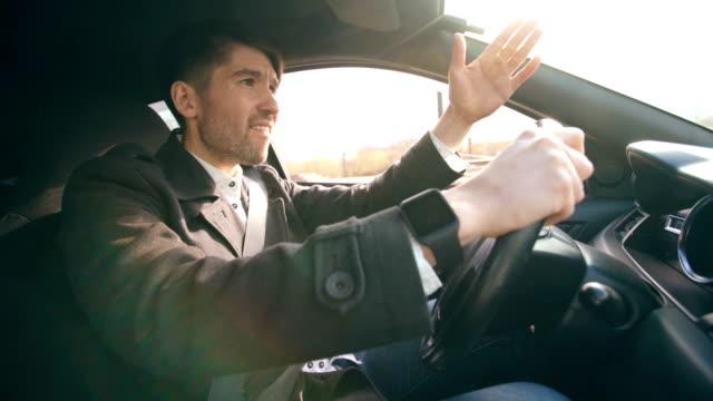 Hombre-de-negocios-joven-conduciendo-coche-muy-molesto-y-destacó-después-fracaso-duro-y-móvil-atasco-de-tráfico
