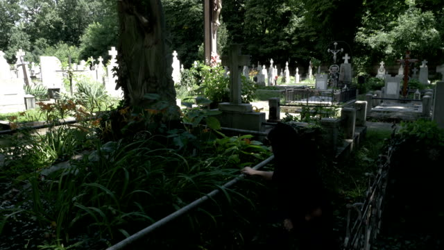 Pained-funeral-woman-widow-placing-a-crown-on-old-grave-with-statue-covered-in-moss-ivy-and-weeds-crying-down-her-knees