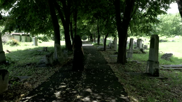 Funeral-gothic-widow-woman-in-black-holding-a-crown-in-hand-walking-in-the-old-cemetery-alley-filled-with-fallen-tree-leaves