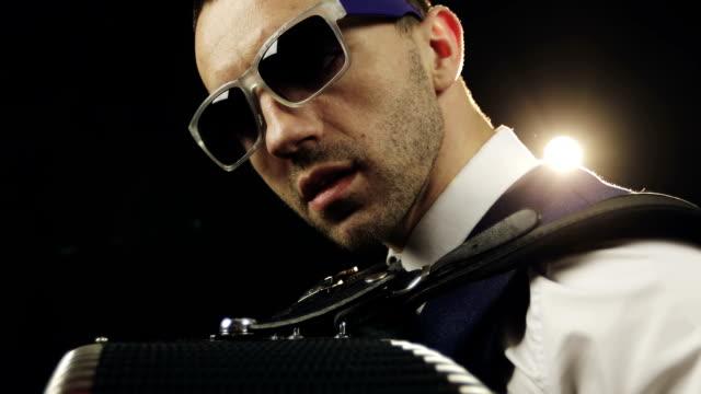 Close-up-La-cara-del-músico-en-gafas-de-sol-en-una-brillante-luz-trasera-