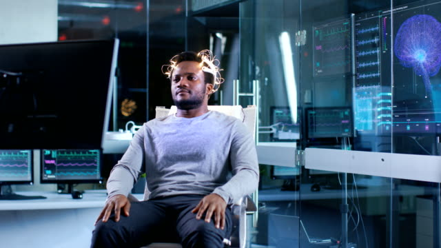 Man-Wearing-Brainwave-Scanning-Headset-Sits-in-a-Chair-while-Watching-Stimulating-Images-on-Display-In-the-Modern-Brain-Study-Laboratory-Monitors-Show-EEG-Reading-and-Brain-Model-