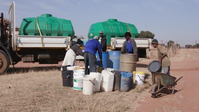 Los-africanos-recolectando-agua-en-recipientes-de-una-cisterna-de-agua-debido-a-la-sequía-en-África-del-sur