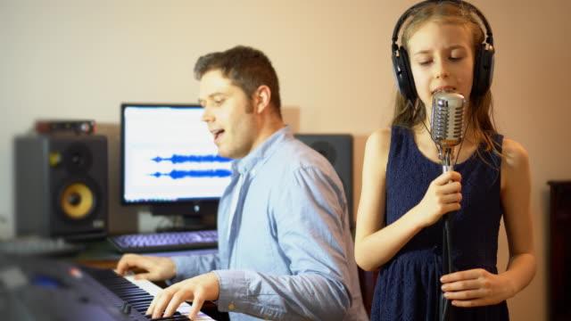 Hombre-con-niña-ensayando-la-canción-en-estudio-de-música-
