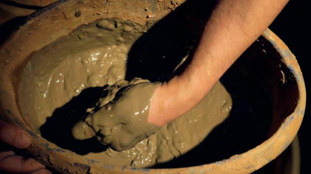 Un-primer-plano-de-una-mano-de-alfareros-mezcla-arcilla-húmeda-