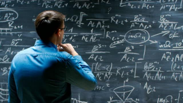 Joven-matemático-enfoques-pizarra-grande-brillante-y-acabados-escribir-fórmula-da-vuelta-alrededor-y-sonríe-a-cámara-