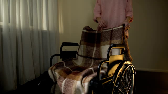 Woman-taking-away-empty-wheelchair-thinking-about-mother-sorrow-for-beloved