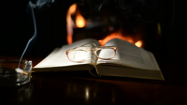 Open-book-on-table-in-front-of-burning-fireplace