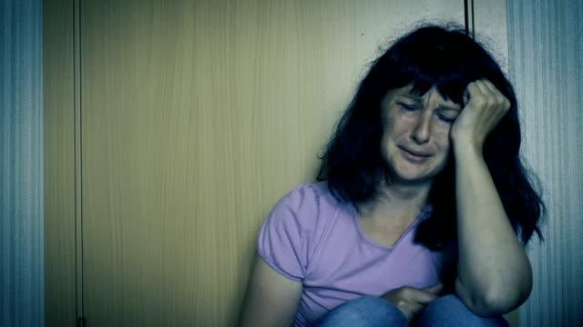 Violencia-en-la-familia-Joven-mujer-violada-llora-sentado-en-el-piso-en-la-esquina-de-la-habitación-Cerca-de-una-mujer-asustada-y-llora-con-manchados-hacen-para-arriba-Chica-llorando-en-la-esquina-y-sentirse-solo-