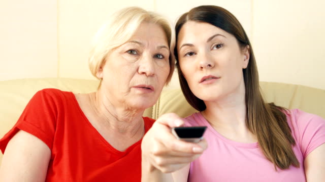Mother-and-daughter-relaxing-on-sofa-at-home-watching-TV-Switching-channels-with-remote-control