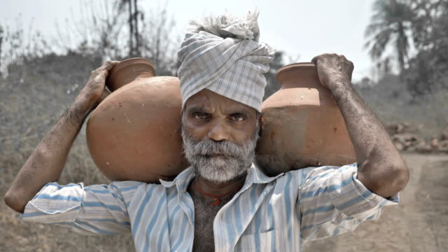 Tired-poor-man-carrying-clay-pots-and-standing-in-barren-farmland-under-the-hard-sun