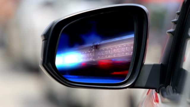 Flashing-emergency-siren-lights-on-rescue-truck-in-side-view-mirror-car