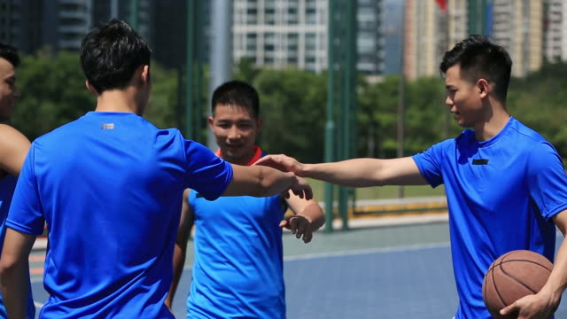 asian-young-basketball-team-players-showing-unity
