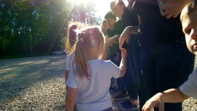 Adolescentes-y-niños-equipos-saludándose-con-estrechan-la-mano-en-el-día-soleado-de-verano