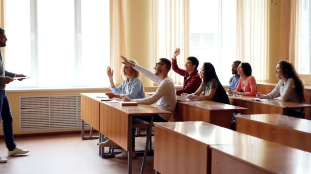Jóvenes-estudiantes-son-levantando-manos-y-respondiendo-a-las-preguntas-del-profesor-y-barbudo-profesor-de-hombre-es-hablar-y-gesticular-Ambiente-luz-de-la-habitación-