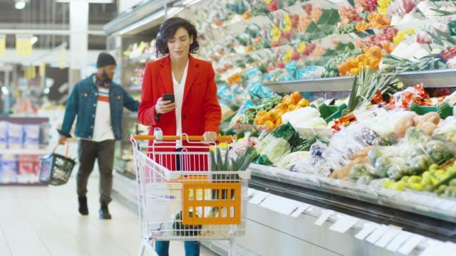 En-el-supermercado:-hermosa-joven-con-carrito-de-compras-utiliza-Smartphone-y-caminatas-a-través-de-fresco-producen-sección-de-la-tienda-
