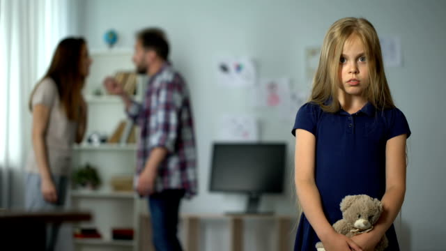 Sad-little-girl-looking-her-parents-arguing-on-background-problems-in-family