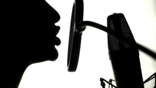 Silueta-de-una-mujer-cantando-una-canción-en-un-estudio-de-grabación