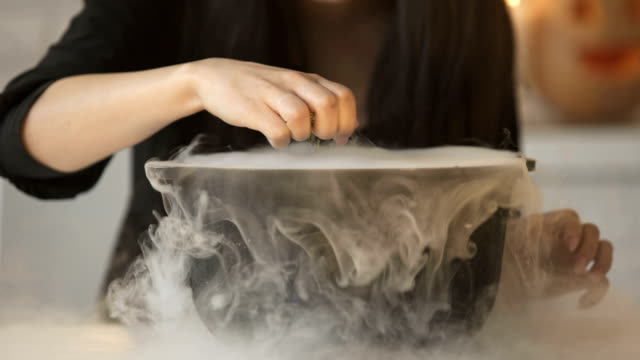 Witch-conjuring-putting-magic-spell-and-cooking-potion-in-pot-with-white-smoke