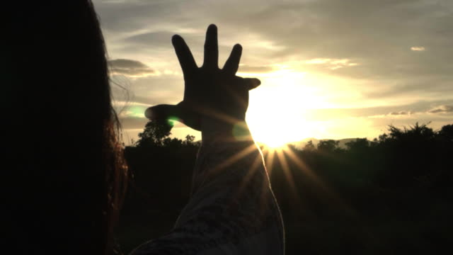 Sunlight-through-female-hands-while-her-looking-at-sun