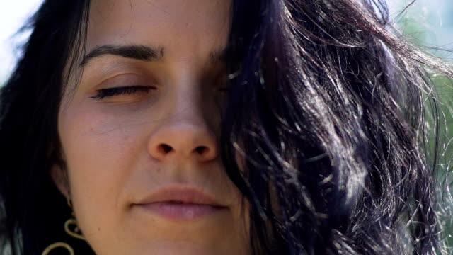 Mujer-con-el-pelo-oscuro-medita-con-los-ojos-cerrados-al-aire-libre-unicidad-del-templo-interior
