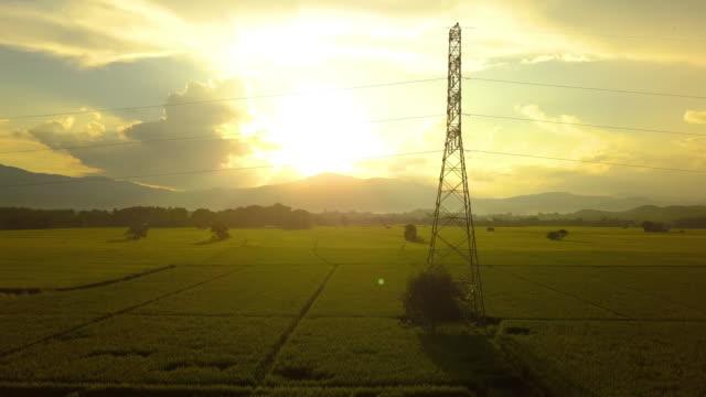 Vuelo-hacia-arriba-y-alrededor-de-la-torre-de-electricidad-de-alto-voltaje-con-la-puesta-del-sol