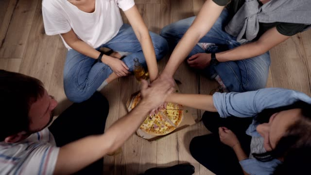 Vista-superior-de-jóvenes-que-mano-a-mano-en-la-caja-de-pizza-entonces-tomar-rebanadas-de-pizza-sabroso-caliente-de-la-caja-de-cartón-Colocación-de-piso-de-madera-bebidas-y-pizza-en-el-piso