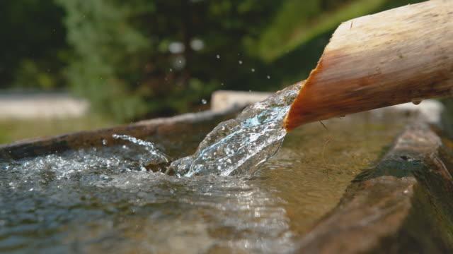 LENTA:-agua-cristalina-corriente-fluye-a-través-de-la-tubería-de-madera-en-Cuenca