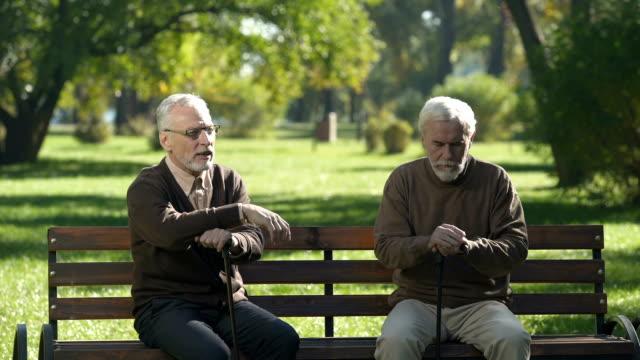 Zwei-alte-Männer-von-Bank-aufstehen-und-gehen-unterschiedlich-Streit