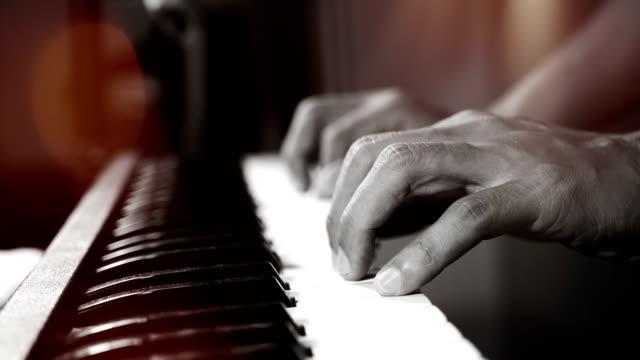 Imágenes-de-4K-de-manos-de-la-pianista-de-música-tocando-el-piano-en-el-club-de-noche-con-foco-y-luz-bokeh-enfoque-selectivo-de-instrumento-musical-piano-magnífico-con-profundidad-de-campo