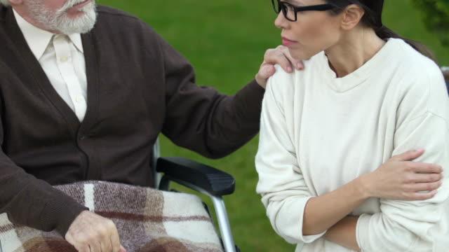 Hija-llorando-cerca-de-viejo-padre-en-silla-de-ruedas-presionado-con-noticias-sobre-el-cáncer