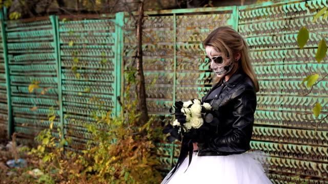 Creepy-novia-con-un-ramo-de-flores-negras-y-el-maquillaje-en-forma-de-un-cráneo