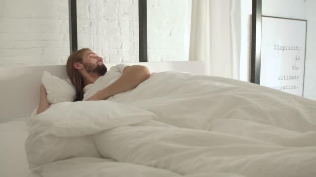 Hombre-para-dormir-despertar-hasta-mañana-en-la-cama-con-sábanas-blancas