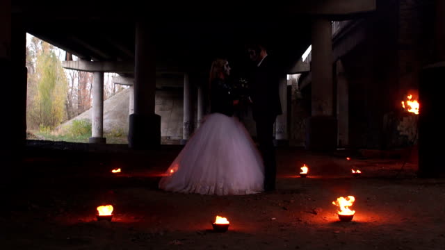 Scary-couple-with-creepy-makeup-on-Halloween-with-fire-and-burning-torches-