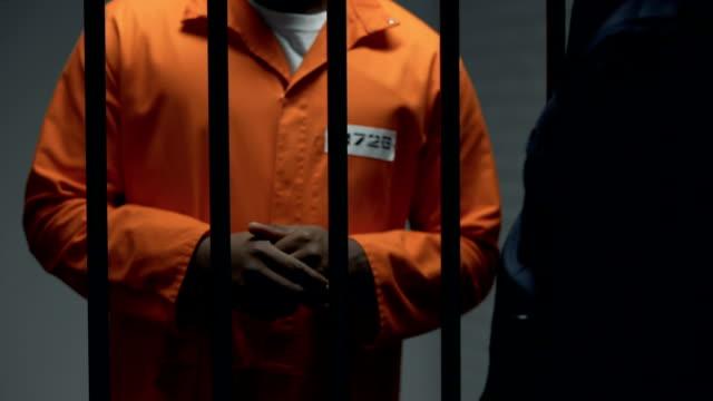 Corrupt-officer-giving-black-imprisoned-criminal-blade-revolt-preparation