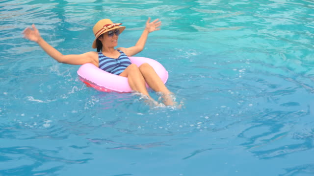 Girl-playing-and-swimming-on-ring-rubber-floating-on-swimming-pool