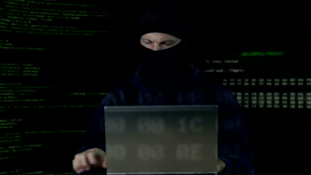 Criminal-in-mask-checking-surveillance-camera-on-laptop-and-phone-database