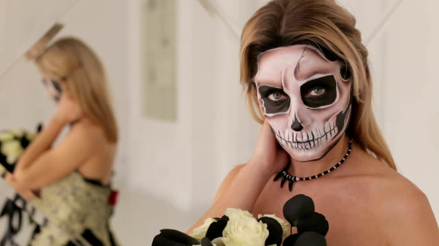 A-young-blonde-in-a-black-dress-and-makeup-in-the-form-of-a-skeleton-Halloween-