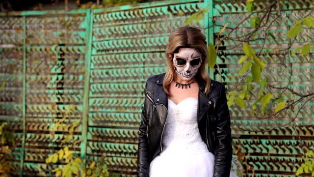 Chica-con-un-maquillaje-espeluznante-para-Halloween-en-el-fondo-de-una-vieja-valla-oxidada