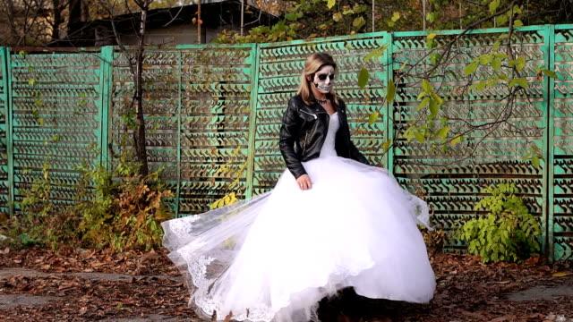 Chica-en-vestido-de-novia-con-un-terrible-maquillaje-girando-en-el-otoño-Víspera-de-Todos-los-Santos