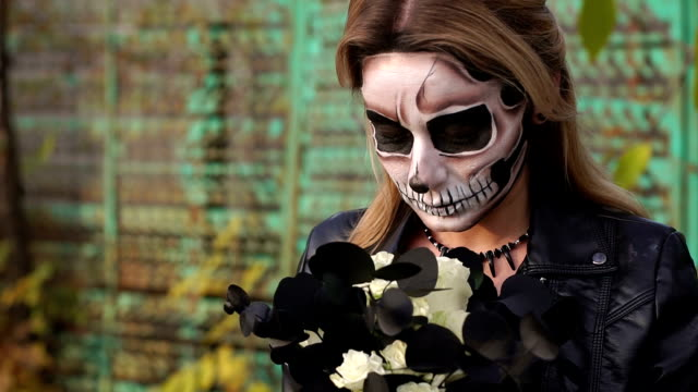Novia-espeluznante-con-un-ramo-de-flores-negras-y-maquillaje-en-forma-de-cráneo-