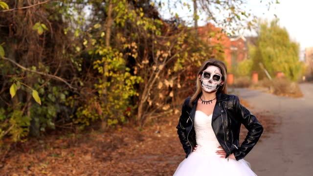 Una-joven-con-un-maquillaje-espeluznante-en-forma-de-cráneo-en-un-camino-vacío-